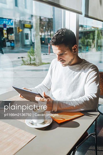 Young man using tablet computer in cafe - p1166m2136792 by Cavan Images