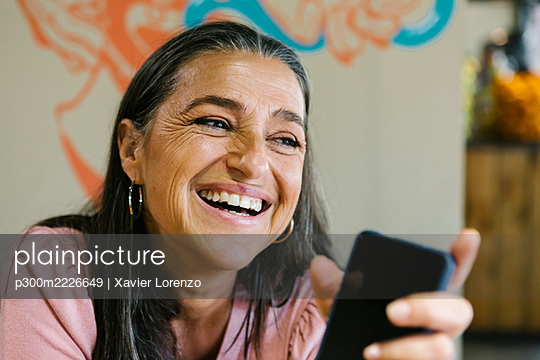 Cheerful woman holding smart phone while sitting at bar - p300m2226649 by Xavier Lorenzo