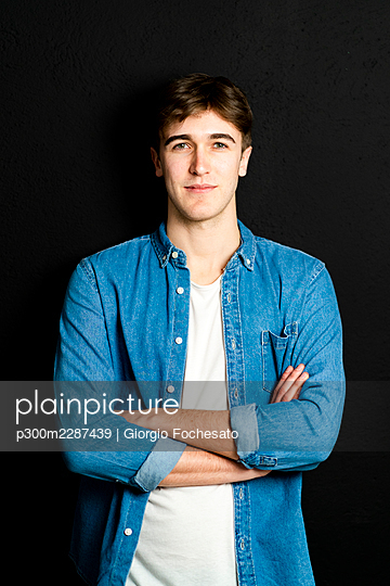 Handsome man with arms crossed standing against black background - p300m2287439 by Giorgio Fochesato