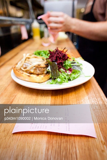Dinner order ticket with burger and salad on plate. - p343m1090002 by Monica Donovan