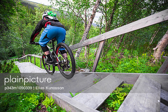 Mountain biker riding down a long staircase built for hikers in the north of Sweden. - p343m1090339 by Elias Kunosson