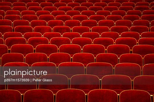 Reihe roter Stühle in einem Theater - p397m1573939 von Peter Glass