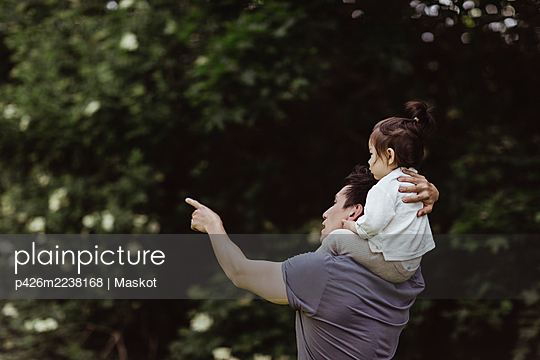 Father pointing while carrying male toddler over shoulder at park - p426m2238168 by Maskot