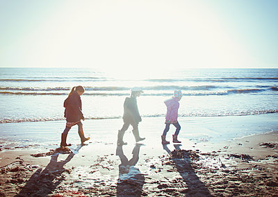 Brother and sisters in warm clothing walking in wet sand on sunny beach - p1023m1406978 by Sam Edwards