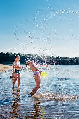 Children splashing with water at lakeshore - p300m1499382 by Jana Mänz