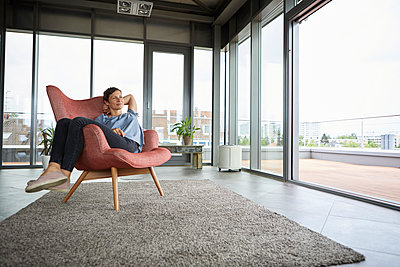Woman sitting in armchair at home relaxing - p300m2012977 von Rainer Berg