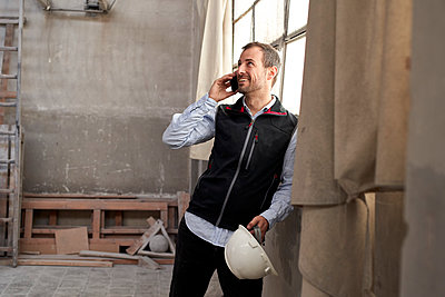 Smiling male contractor talking over smart phone while standing in building - p300m2243418 by Veam