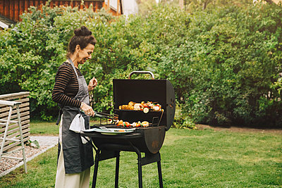Side view of smiling woman cooking dinner on barbecue grill at back yard during garden party - p426m2194895 by Maskot