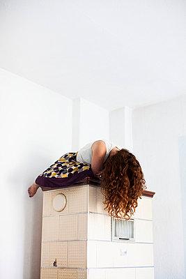 Frau auf einem Kachelofen - p586m855800 von Kniel Synnatzschke