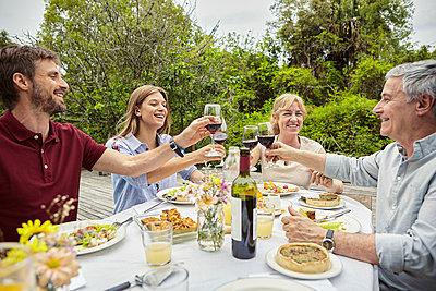 Happy family toasting wine glasses - p623m2258070 by Dinoco Greco