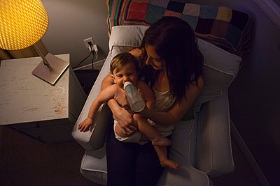 High angle view of mother in armchair feeding baby boy from baby bottle - p924m1081812f by Raphye Alexius