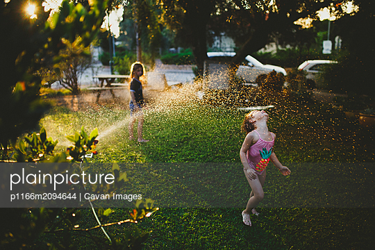 Two girls wearing bathing suit playing on the grass with sprinkler - p1166m2094644 by Cavan Images