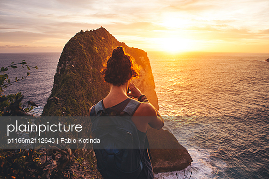 Rear view of man with backpack looking at sea while standing on mountain against sky during sunset - p1166m2112643 by Fabio Kotinda