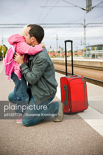 Father and daughter saying goodbye to daughter on railway platform - p31227799 by Susanne Kronholm