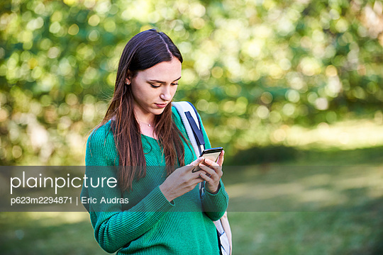Young woman text messaging on smart phone - p623m2294871 by Eric Audras