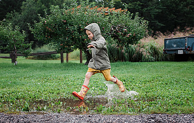 Playful boy jumping and splashing water in puddle at apple orchard - p1166m2024800 by Cavan Images