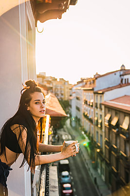 Beautiful young woman on balcony above the city at sunset with cup of coffee - p300m2042256 von Kike Arnaiz