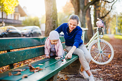 Mother and daughter taking a break on a park bench - p300m2059899 by Daniel Ingold
