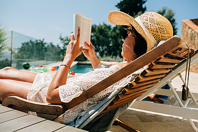 Woman reading on sunchair - p312m1557175 by Anna Rostrom