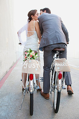 Young newlywed couple kissing on bicycles in street - p92412059 by Steven Lam