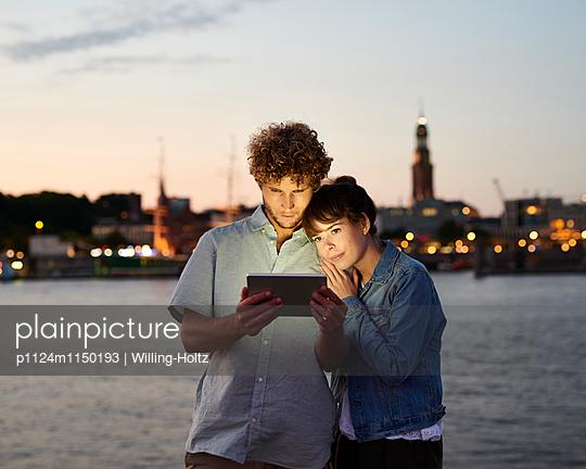 Paar mit Tablet abends an der Elbe  - p1124m1150193 von Willing-Holtz