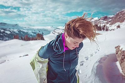 Hiker standing on snowy field against cloudy sky - p1166m1209372 by Cavan Images