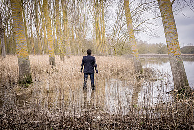 Man in suit is standing in the river - p1402m1516648 by Jerome Paressant