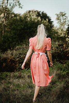 Young woman in pink dress and white apron, rear view - p1628m2211986 by Lorraine Fitch