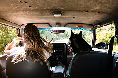 Woman with long blond hair driving by husky on road trip - p300m2202715 by Jose Luis CARRASCOSA