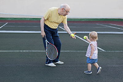 Girl giving tennis ball to grandfather while standing at playing field - p301m1180616 by Vladimir Godnik