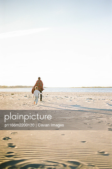 A little boy and his father playing tag at the beach - p1166m2200130 by Cavan Images