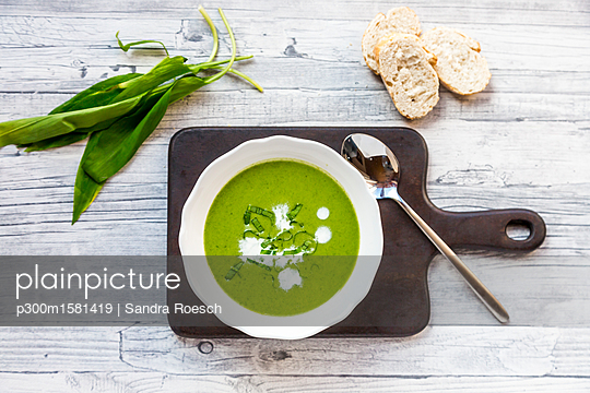 Dish of ramson soup garnished with ramson and cream - p300m1581419 von Sandra Roesch