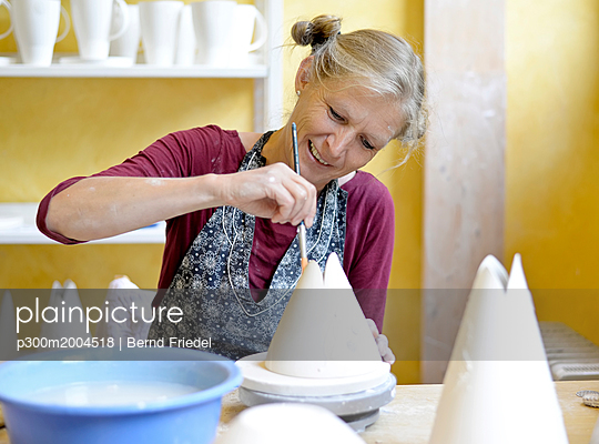 Smiling woman working on porcelain in workshop - p300m2004518 von Bernd Friedel