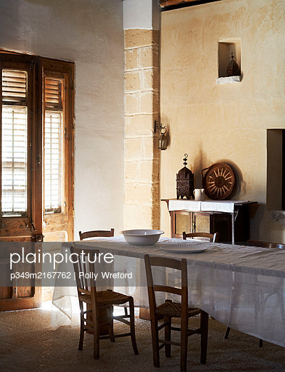 Wooden chairs at table with white cloth in sunlit doorway of traditional Sicilian home - p349m2167762 by Polly Wreford