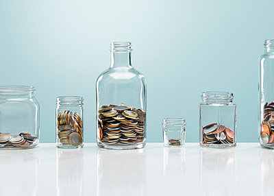 Coins in variety of glass bottles - p1023m2135761 by Andy Roberts