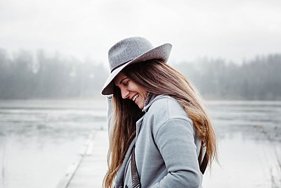 profile of a woman with long brown hair and a hat on laughing smiling - p1166m2163477 by Cavan Images