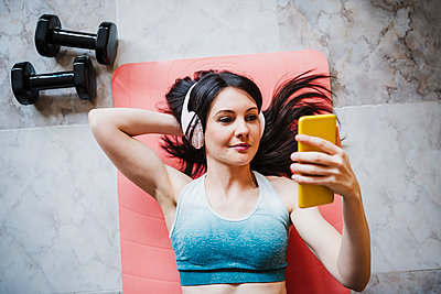 Woman using smart phone while relaxing on exercise mat at home - p300m2274175 by Eva Blanco