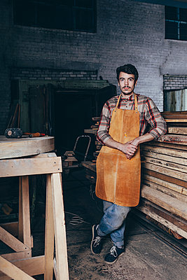 Portrait of carpenter standing by timber stack in workshop - p301m1196887 by Vasily Pindyurin