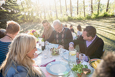 Three generations of family having a meal outdoors. - p328m784066f by Hero Images