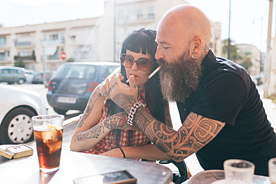 Mature hipster couple lighting cigarette at sidewalk cafe, Valencia, Spain - p429m1557450 by Eugenio Marongiu
