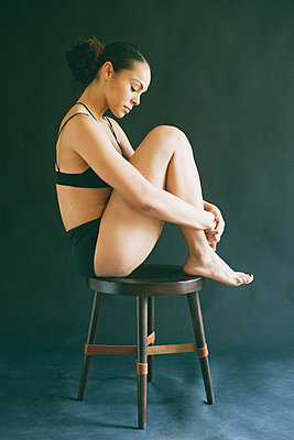 Mixed Race woman wearing underwear sitting on stool - p555m1491129 by Peathegee Inc