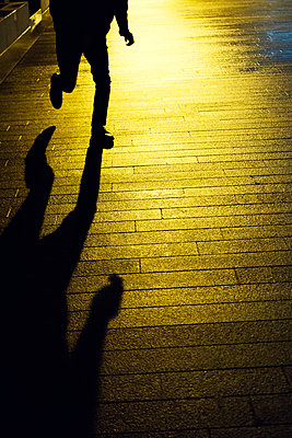 Man running on the street at night  - p794m2064409 von Mohamad Itani