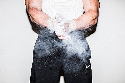Sportler reibt Hände mit Talkum ein - p930m1200523 von Phillip Gätz