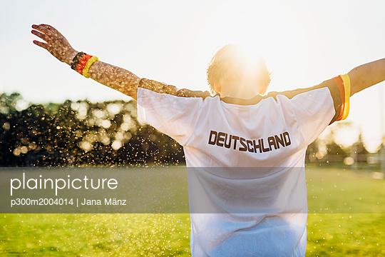 Cheering boy wearing football shirt with Germany written on back - p300m2004014 von Jana Mänz