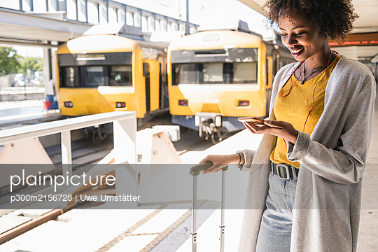 Smiling young woman with earphones and smartphone at platform - p300m2156728 by Uwe Umstätter