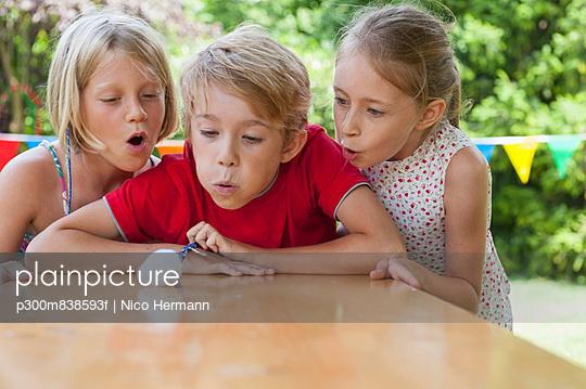 Children blowing cotton ball on garden table
