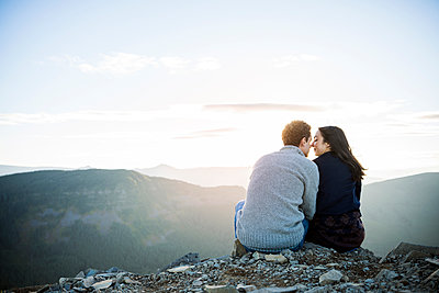 Rear view of couple sitting on rocks at mountain cliff - p1166m1142883 by Cavan Images