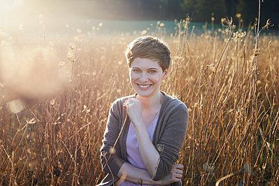 Portrait of smiling woman relaxing in nature - p300m2005441 von Philipp Nemenz