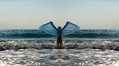 Silhouette of young woman in front of the sea holding blue cloth with outstretched arms - p300m950253f by Andreas Jontsch