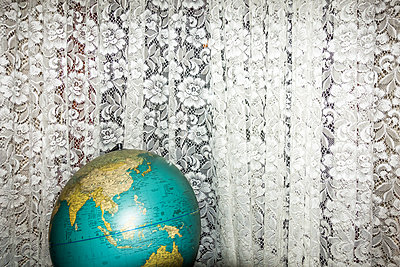 Globe in front of curtain - p354m2108556 by Andreas Süss